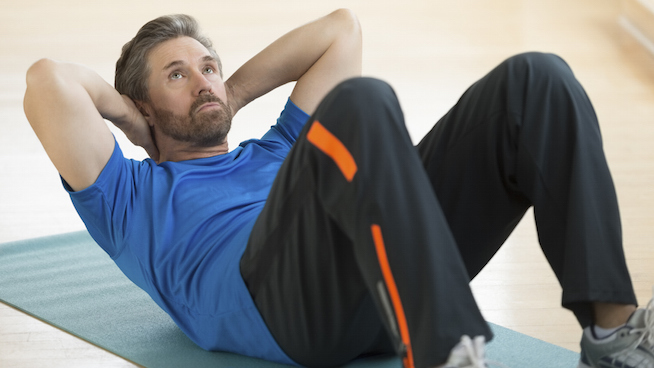 Man Doing Sit-Ups On Exercise Mat