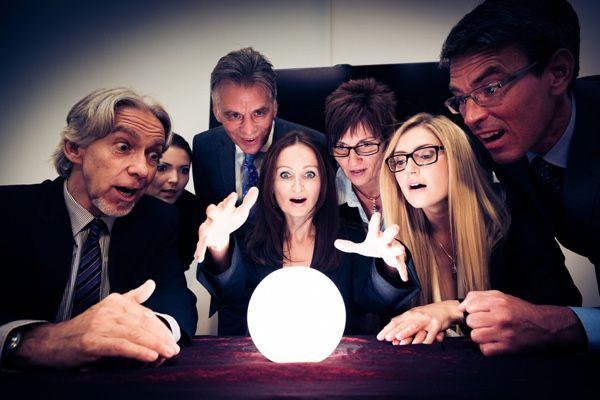 Grupo de personas sorprendidas alrededor de una esfera de luz sobre una mesa