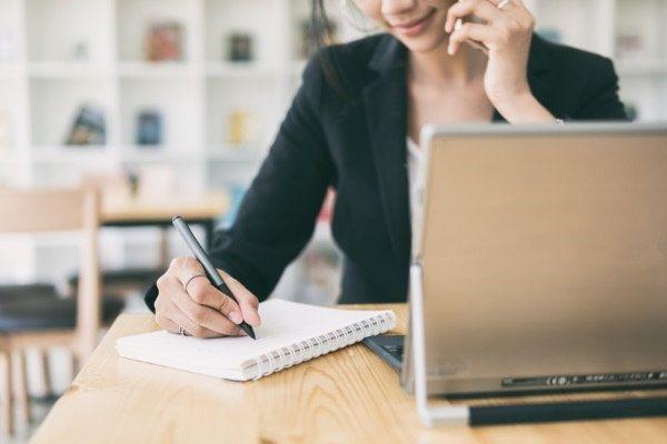 Mujer trabajando sobre listas de recordatorios en un cuaderno