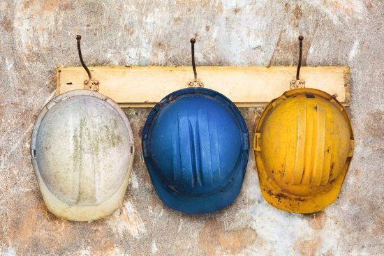 Tres sombreros de obra colgados en perchas que simbolizan los tres tipos de trabajo para los profesionales del conocimiento