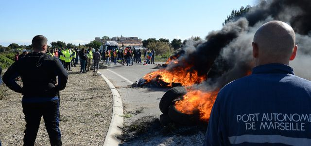 "CGT union's workers block with tire the access to the refinery of Fos-sur-Mer, southeastern France, on May 23, 2016 to protest against the government's planned labour law reforms. Fuel supply difficulties continued May 23 in selected service stations with new blockages despite the government's promise to ""liberate"" the deposits held by opponents of the government's proposed labour reform. Since the evening of May 22 to May 23, several hundred activists from the labour union CGT blocked the fuel depot of Fos-sur-Mer ( Bouches-du-Rhône), along with similar action in the north and west of the country. / AFP PHOTO / BORIS HORVAT"