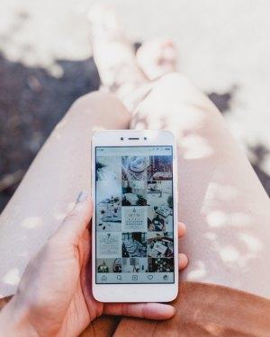 Chica sosteniendo un móvil con la aplicación instagram abierta