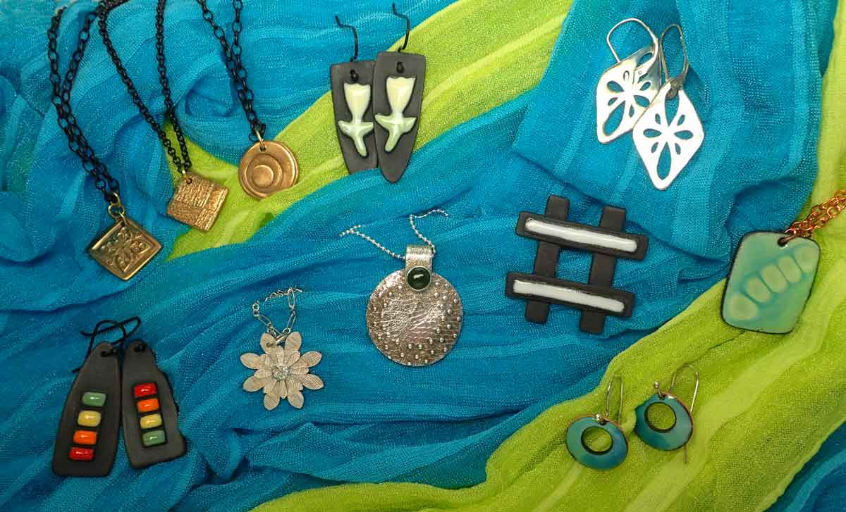 Eleven samples: four earring pairs, one hashtag brooch, six pendants.  Silver, steel, bronze, copper, some with enamel.