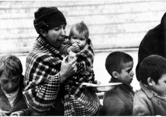 Una cola, en Barcelona, a la espera de alimentos, mientras madre hijo mordisquean un mendrugo. - (Archivo Basilio Martín Patino).