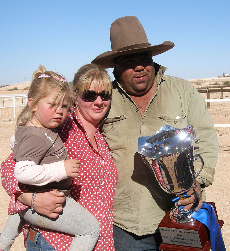 Dion Khan, Lolly Williams and Lacy Khan from Stuart Creek Station holding the Opal Inn Cup and their winning sash