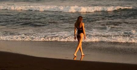 giovane donna passeggia in riva al mare tramonto