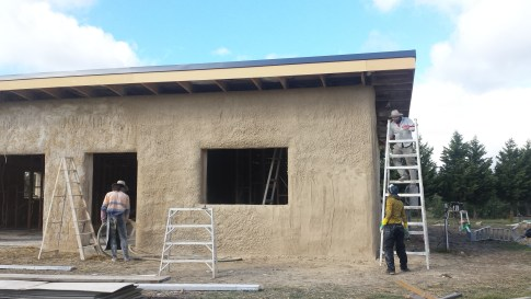 Three stages of the second coat: pumping the render, render on the wall and trowelled render