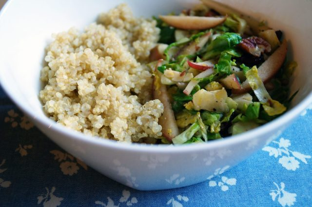 The finished dish in a white bowl with cooked quinoa.