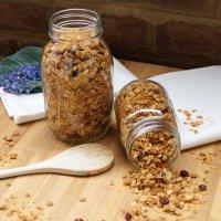 Homemade Maple Walnut Granola in mason jars on a cutting board