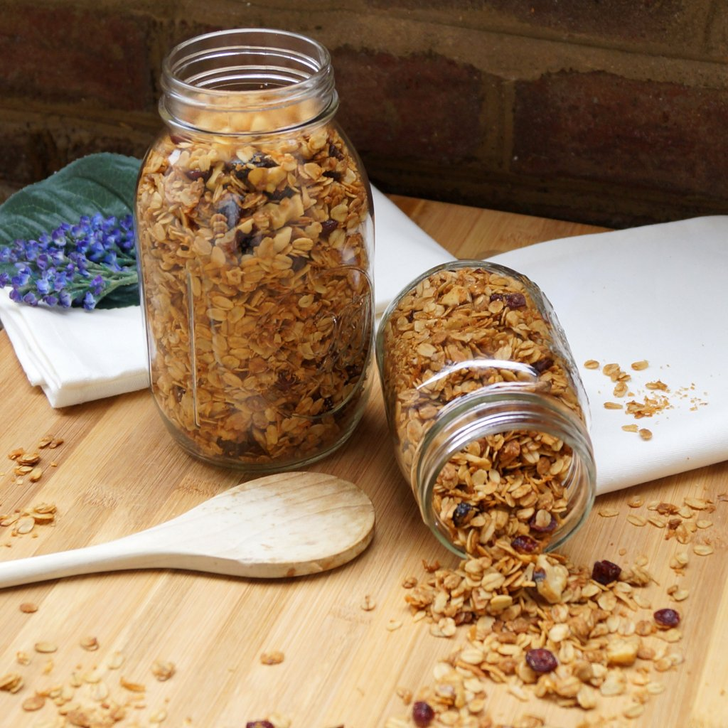 Homemade Maple Walnut Granola in mason jars on a cutting board