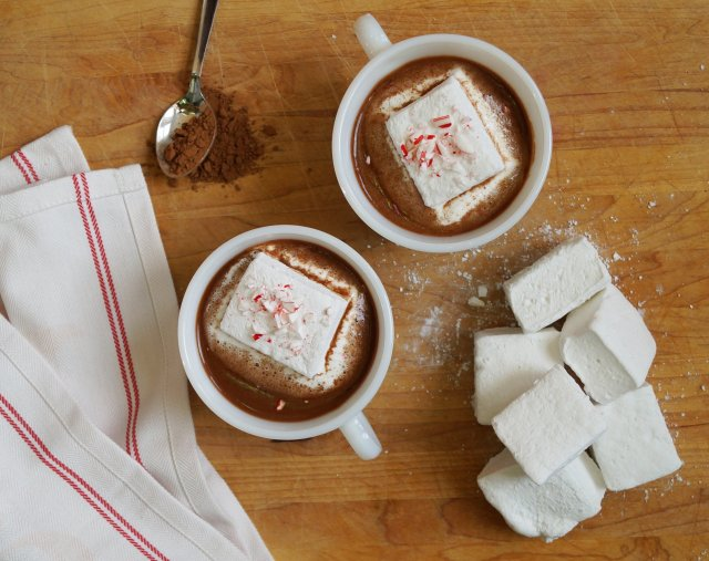 Two white cups on a cutting board filled with hot cocoa and topped with one large peppermint marshmallow and some crumbled candy canes.