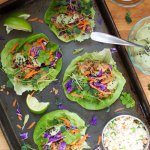 A sheet pan with four lettuce wraps topped with ground turkey, red cabbage, carrots, herbs, and served with dipping sauces.