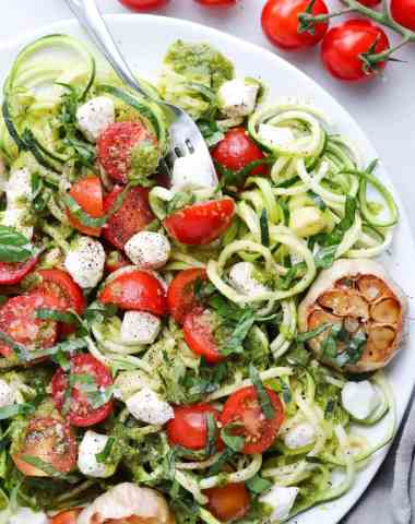 Close up of a plate of spiralized zucchini topped with pesto, mozzarella, tomatoes, and roasted garlic.