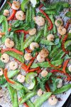 A sheet pan dinner with shrimp, snow peas, and red bell peppers, topped with sesame seeds and fresh cilantro.