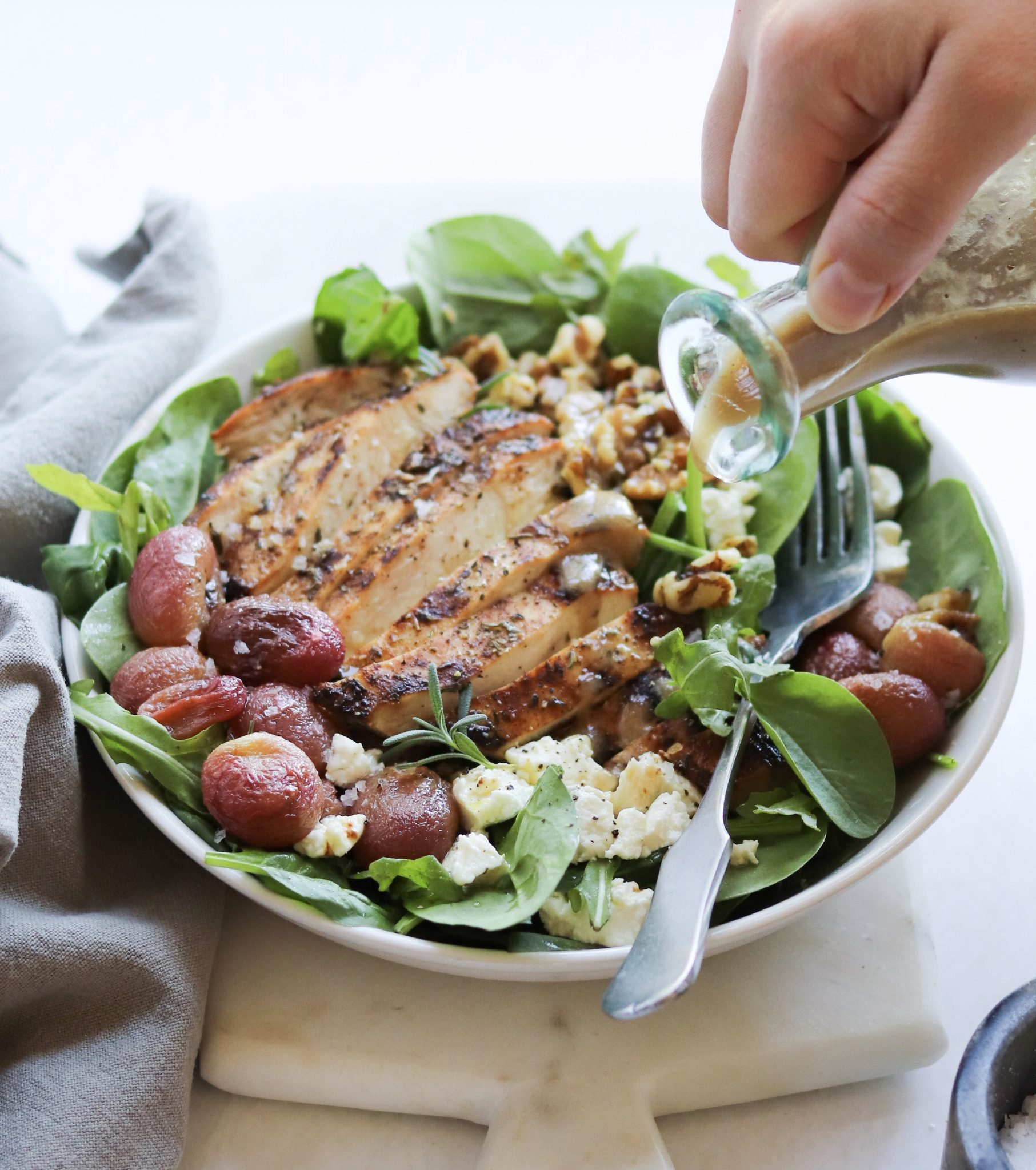 A hand pouring salad dressing from a glass bottle onto a completed dish with grilled chicken, spinach salad, and other toppings