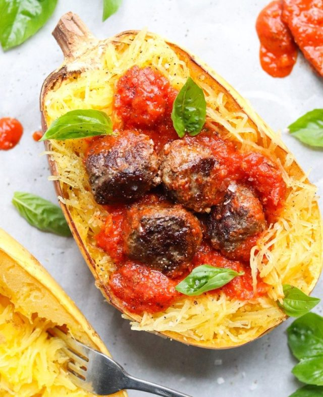 Roasted Spaghetti Squash cut in half and stuffed with meatballs, red marinara sauce, and topped with fresh basil.