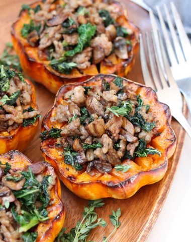 A wooden platter with roasted acorn squash halves stuffed with kale, mushrooms, and ground sausage. Finished Dish.