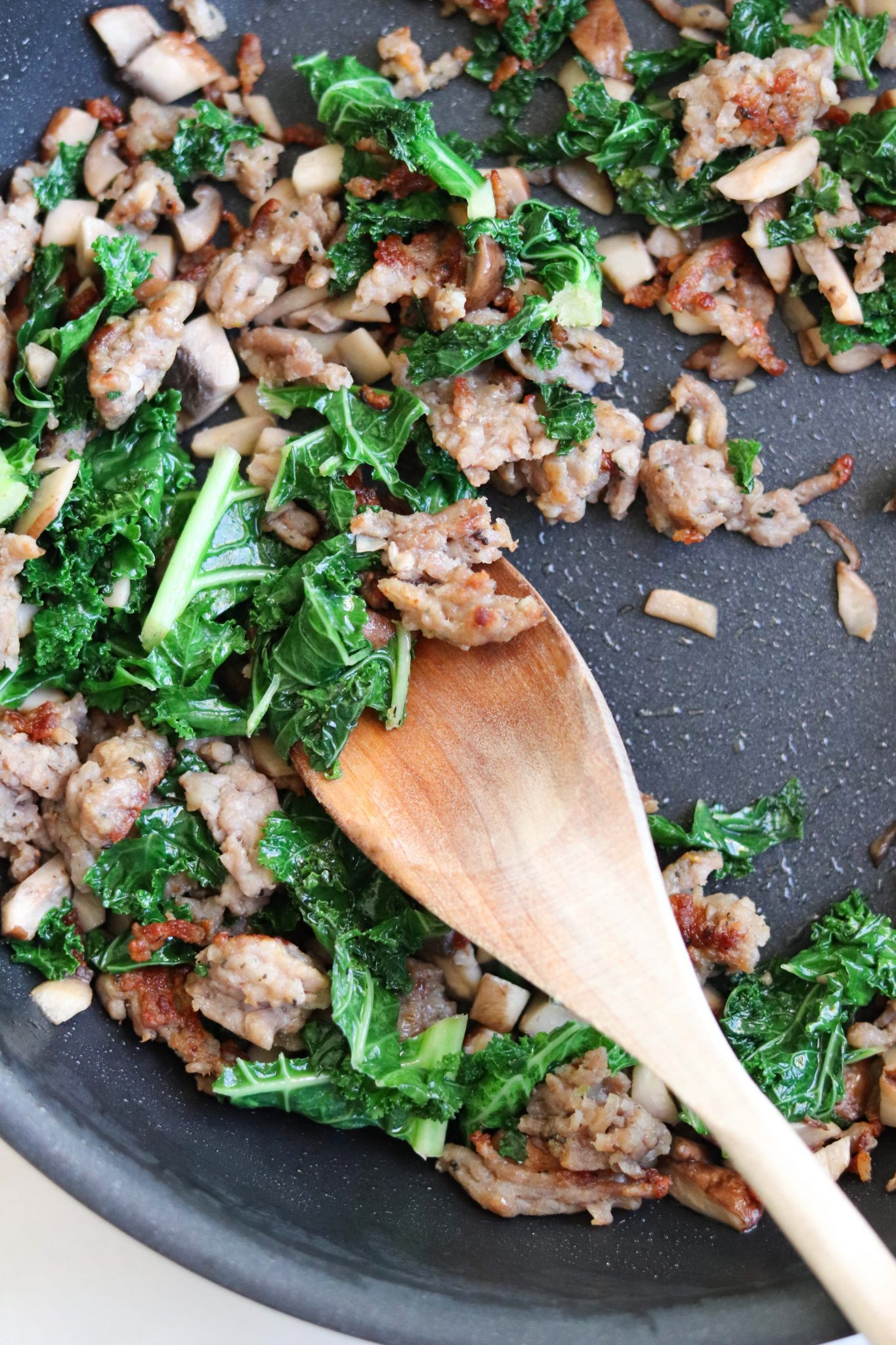 A close up shot of a skillet with ground sausage, kale, and mushrooms cooking.