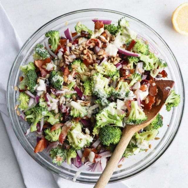 Broccoli Bacon Salad - Finished Dish. A large bowl sits on a white marble board. The bowl is filled with bite sized pieces of broccoli, chopped bacon, sliced red onion, sunflower seeds, and diced dates. A wooden spoon is in the mixture, mixing it up into creamy, crunchy salad goodness!