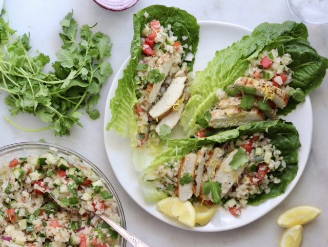 Whole30 Lettuce Boats filled with cauliflower tabbouleh and topped with grilled chicken, herbs, and lemon wedges.