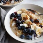 Grain Free oats in bowls topped with berries and bananas
