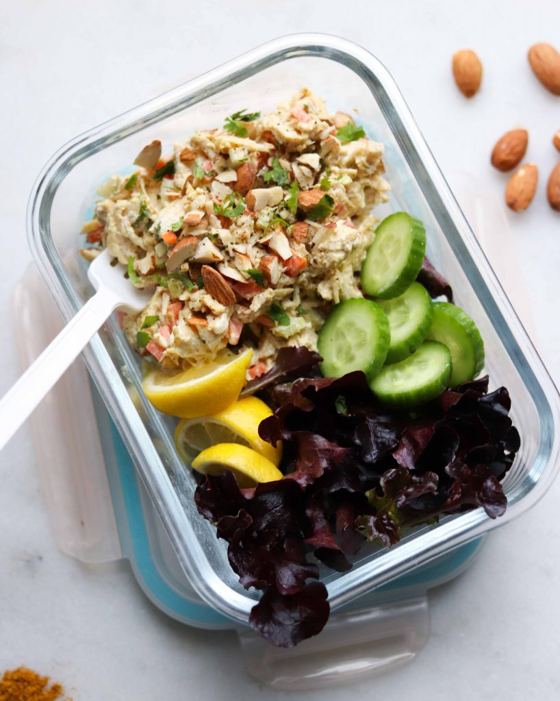 Curry Chicken Salad in a glass meal prep container with a plastic fork. It's served with a few lemon slices, cucumber slices, and torn lettuce leaves.