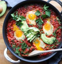 Top down of finished Whole30 Shakshuka with broken, runny yolks and sliced avocado.