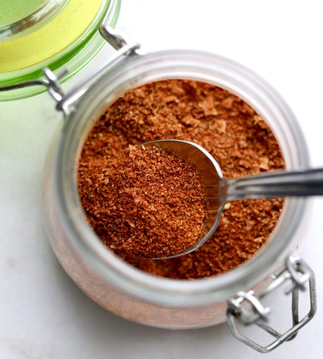 Close up shot of homemade taco seasoning in a glass jar with a spoon inside.