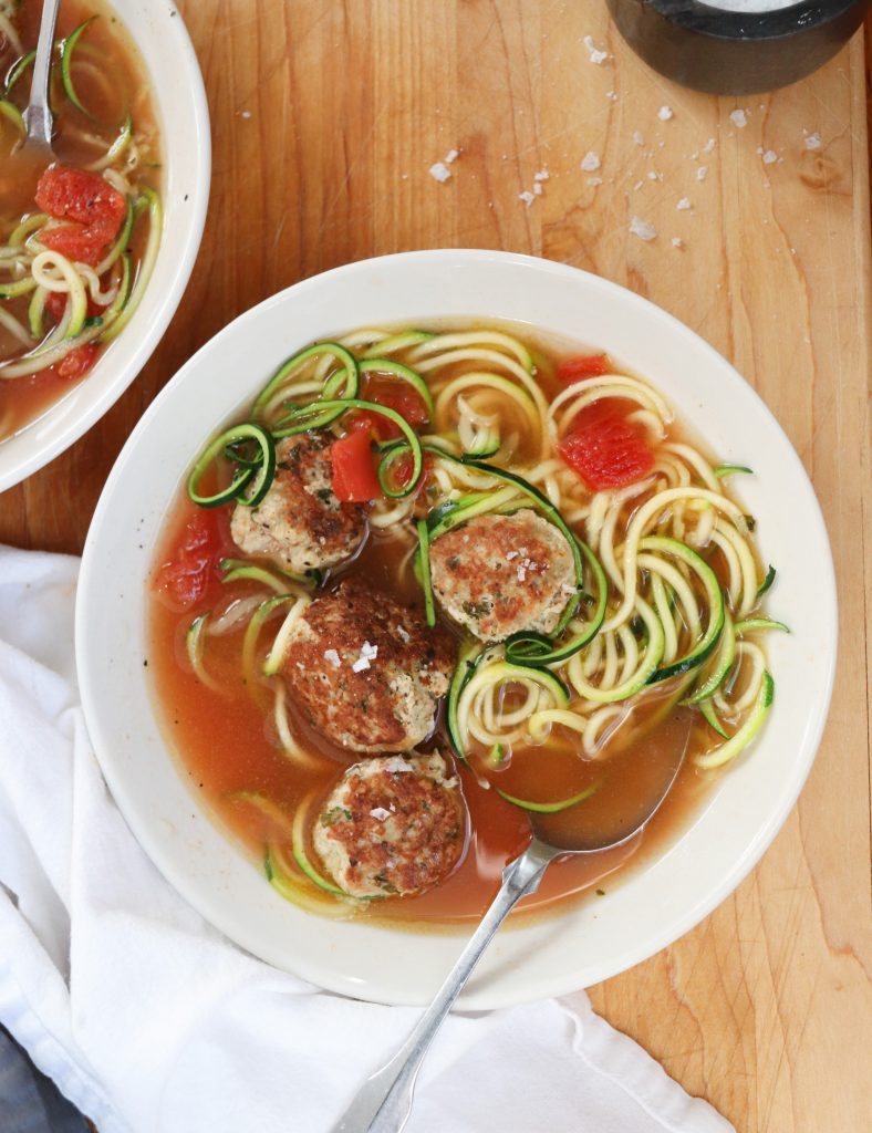 Close up of now bowl of Turkey Meatball & Zoodle Soup in a white bowl on a wooden board.