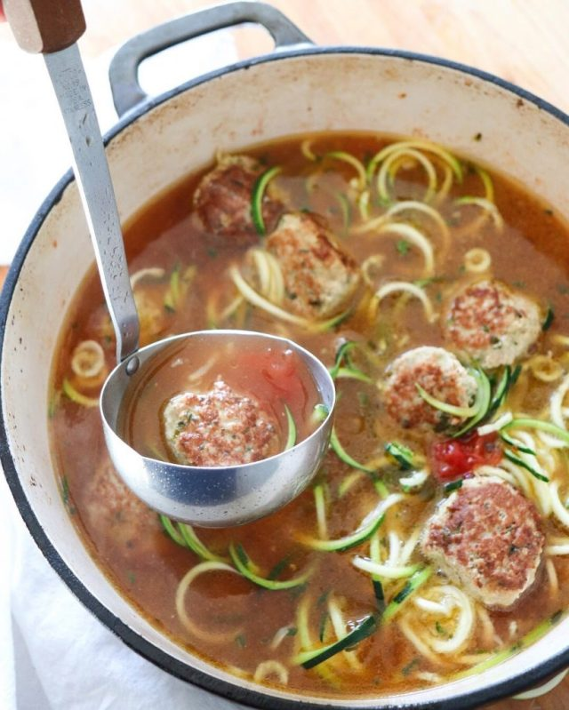 Whole30 Turkey Meatball Soup in a large dutch oven with a ladle.