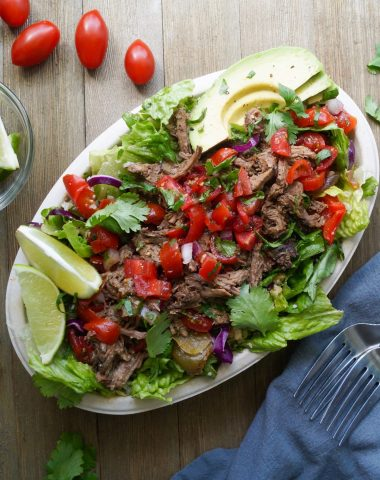 Whole30 Chipotle Barbacoa Bowls. One bowl is on a wooden surface. It's filled with romaine lettuce and topped with shredded barbacoa beef, homemade pico, and cilantro leaves. A few slices of lime and a avocado are beside the salad.
