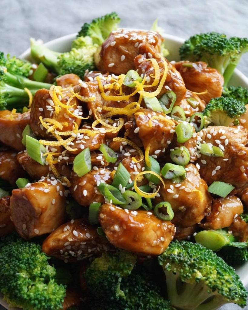 Close up of finished Orange Sesame Chicken and Broccoli, topped with sesame seeds and orange zest.
