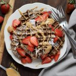 Paleo Chocolate Waffles drizzled with almond butter and topped with sliced strawberries - finished dish