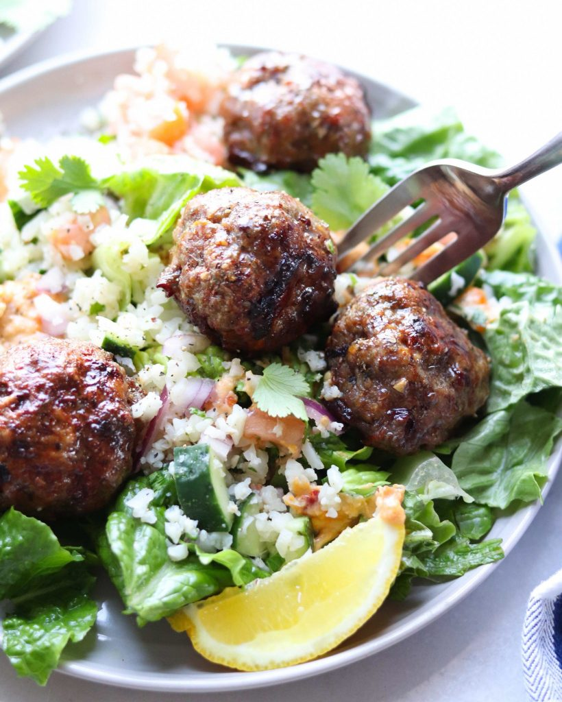 Close up side angle of Whole30 Mediterranean Lamb Meatballs are served on a plate with torn romaine lettuce, cauliflower tabbouleh, hummus and slices of lemon.