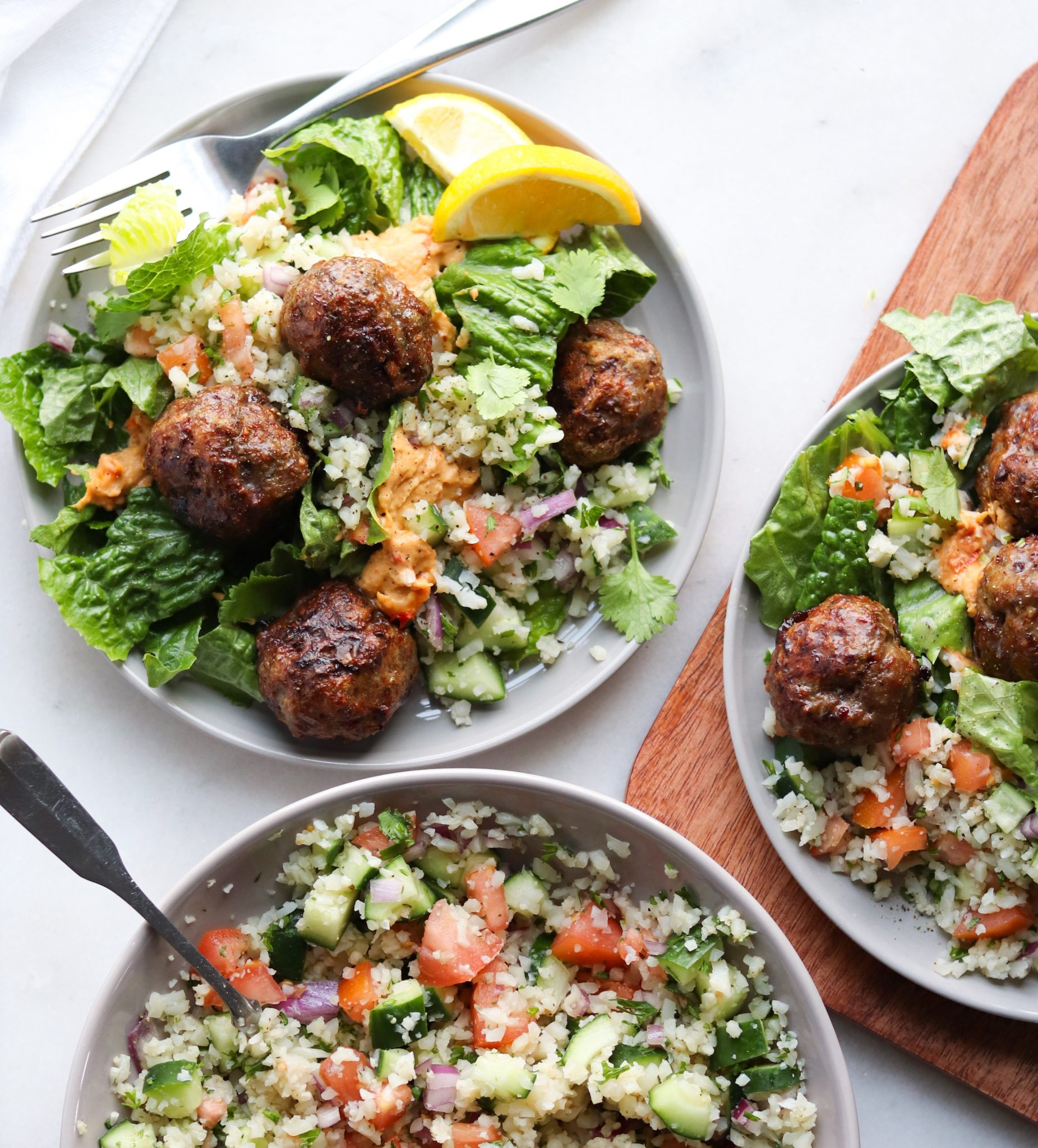 A bowl filled with lettuce, meatballs, red pepper hummus and cauliflower tabbouleh on a white board.
