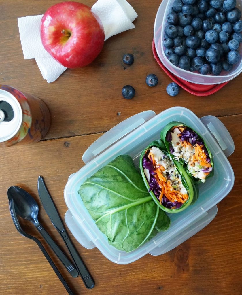Collard Wraps with Chicken Salad in a plastic meal prep container with plastic cutlery.
