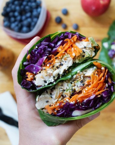 Close up of a hand holding the collard wrap with chicken salad inside.