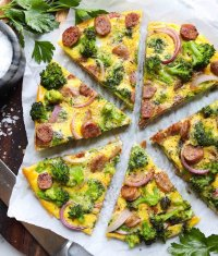 The finished frittata on a brown cutting board, sliced into 6 pieces.
