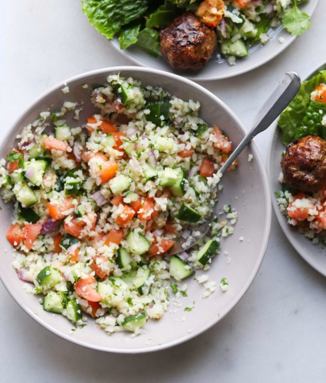 Whole30 Cauliflower Tabbouleh in a gray bowl with a silver spoon.