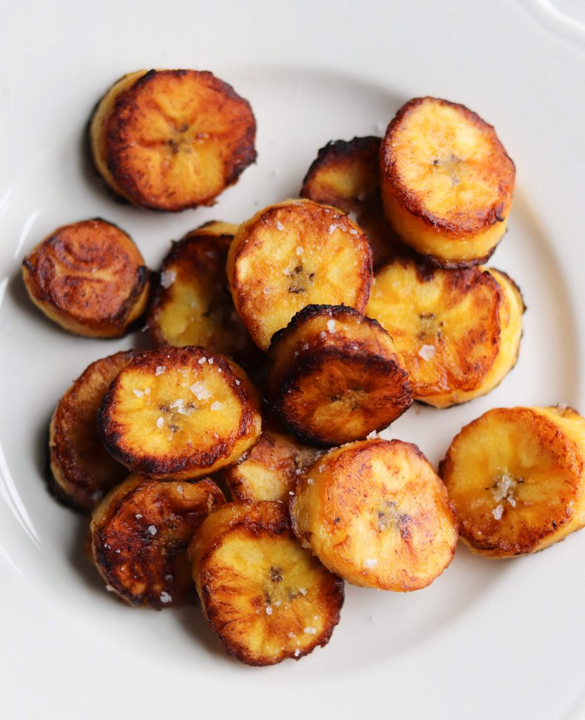 Fried Plantains on a white dish, sprinkled with flakey sea salt.