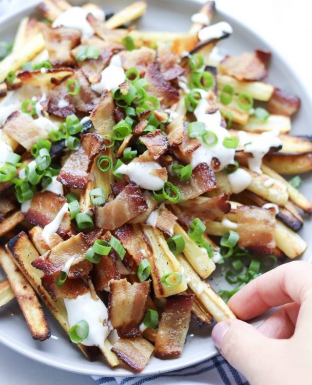 Loaded Roasted Parsnip Fries - Finished Dish. A hand grabs one of the fries.