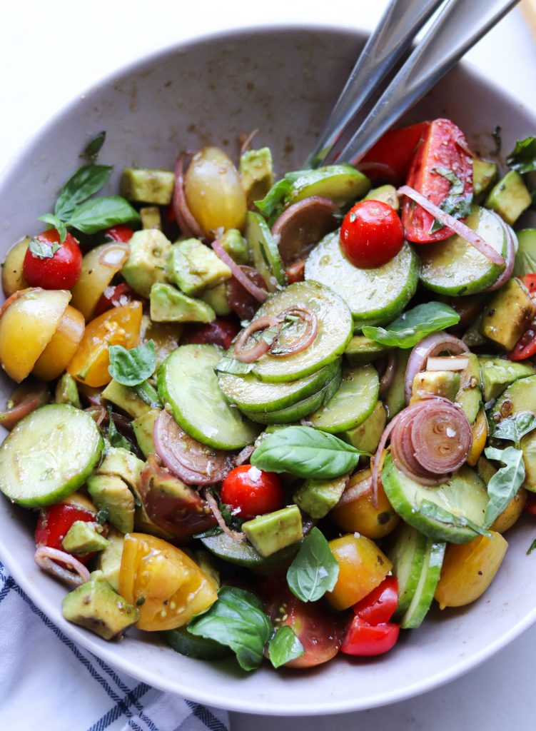 Whole30 Tomato, Cucumber and Avocado Salad - Completed Dish tossed together with the dressing in a large gray bowl. Two large spoons are in the salad, ready to serve!