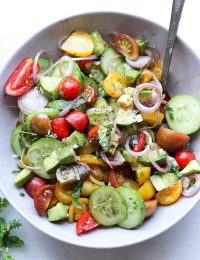 Completed Dish served in a gray bowl with a silver spoon - sliced tomatoes, shallots and avocado all mixed together and drizzled in salad dressing.