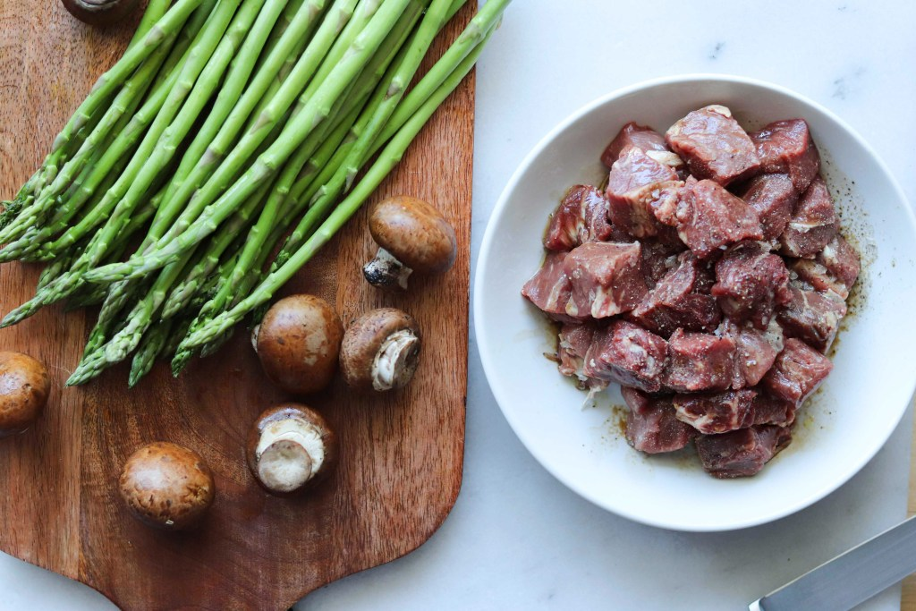 Prep Shot. Steak is cut into bite sized pieces and is marinating in a white bowl. Beside it, mushrooms and asparagus are on a cutting board.