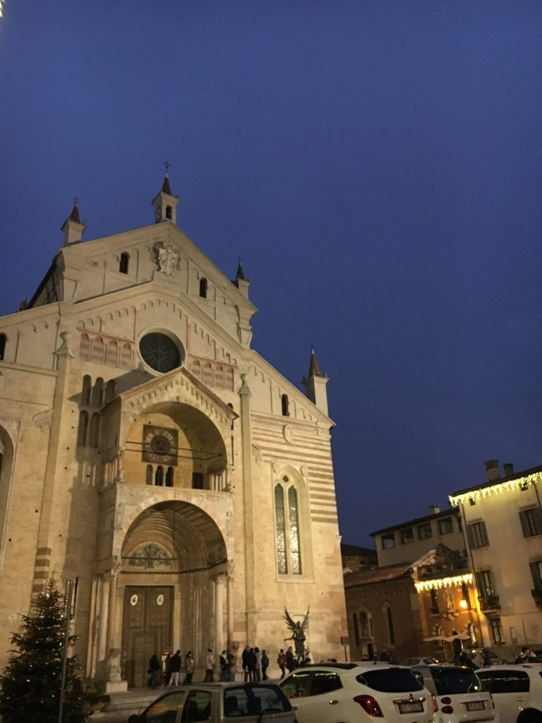 The outside of a massive stone church at dusk with a dark blue sky.