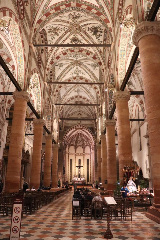 A view of the inside of a massive cathedral from the back down the center aisle.