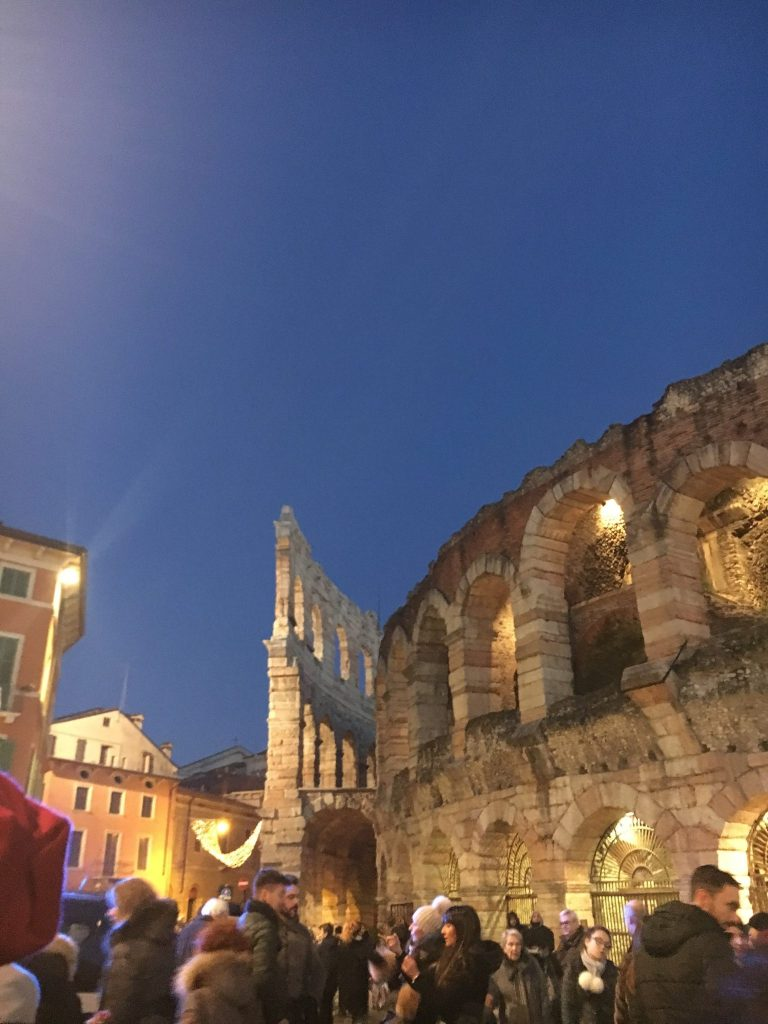 The side of the colosseum in Verona with a clear, dark blue sky at dusk.