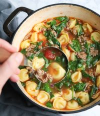 Sausage Tortellini Soup in a large stock pot with a ladel spooning out a large serving.