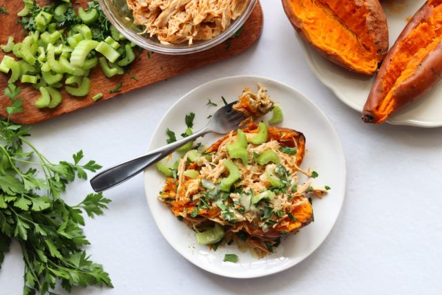A sweet potato is cut open and sits on a white plate. It's topped with shredded buffalo chicken, sliced celery and parsley. Beside it is a cutting board with a bowl of cooked buffalo chicken, more cooked sweet potatoes, and chopped celery.