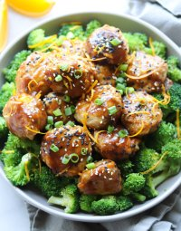 Paleo Orange Chicken Meatballs served over steamed broccoli in a large gray bowl on a white marble board. The meatballs are sprinkled with sliced green onion, orange zest, and sesame seeds.